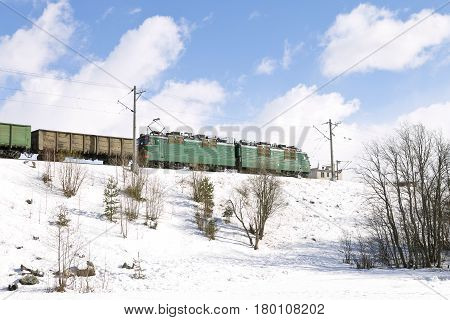 Freight train passing by railways in winter. Northern Russia, railroad through the snow areas