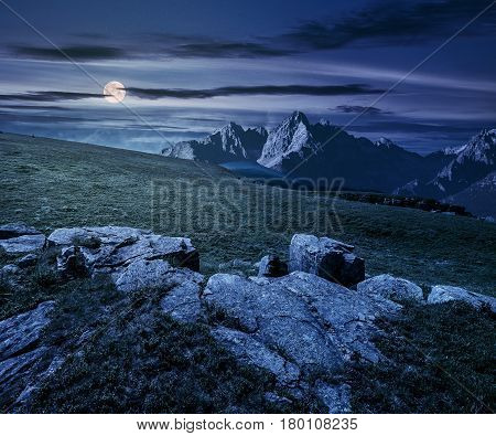 Composite night landscape with full moon. rocky peaks of mountain ridge and rocks on hillside under the dark sky with clouds and stars. picturesque fantasy view.
