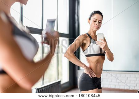 Portrait of proud muscular  woman  taking mirror selfie in gym posing boasting her fit figure and slim waist