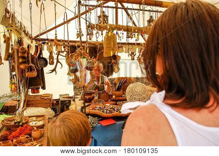 Burghausen,Germany-July 13,2013:People watch a woman create glass beads during the Burgfest Medieval festival in BurghausenGermany