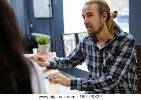 Adolescent man listening to opinion of his co-worker