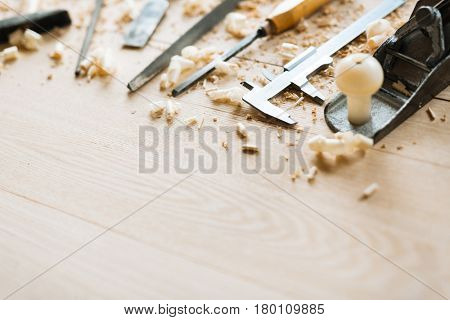 Still life of carpentry tools on wooden table background, shaving scattered everywhere, close-up shot