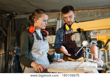 Waist-up portrait of attractive apprentice standing at drill press and listening to her male mentor with attention, he explaining her operating principle of machine