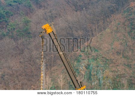 Arm of large drilling machine with drill bit attached at a construction site in South Korea with trees on a mountain side in the background