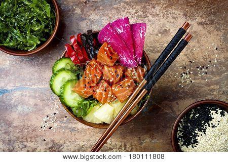 Hawaiian salmon poke bowl with seaweed watermelon radish cucumber pineapple and sesame seeds. Copy space background overhead flat lay