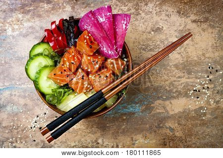 Hawaiian salmon poke bowl with seaweed watermelon radish cucumber pineapple and sesame seeds. Copy space background overhead flat lay