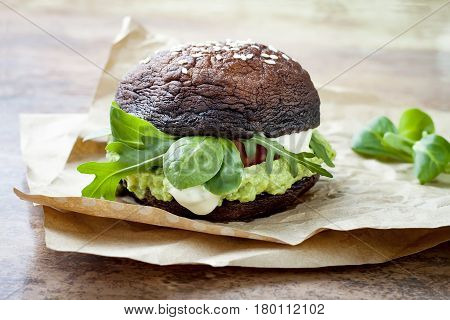 Grilled portobello bun mushroom burger. Vegan gluten free grain free healthy veggies hamburger with guacamole fresh vegetables and cashew cheese sauce.