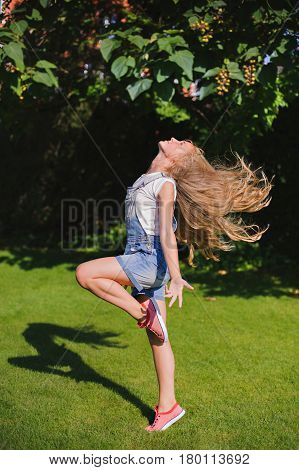 Girl with Long Blowing Hair is jumping at a green park in summer. Glamour Beautiful girl with Healthy and Beauty Blond Hair. Beautiful hair concept.