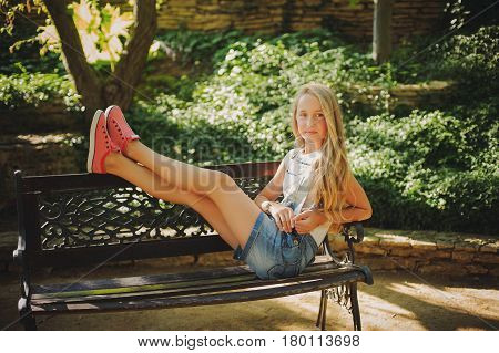 Young girl are sitting on a bench in a park. Blonde female in jeans shorts on the bench with their feet. Rest in park.