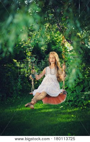 Beautiful blond girl on swing on the park with green plants. Girl with long blond hair in dress on swing. Pretty caucasian young girl on the swing with flowers.