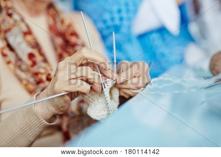 Close-up shot of elderly woman knitting white socks for her little granddaughter with help of three needles, blurred background