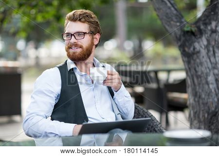 Handsome bearded financial manager enjoying fragrant coffee in lovely outdoor cafe while preparing annual accounting reports on modern laptop, waist-up portrait