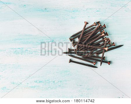 Bronze Screws Over Green Wooden Background
