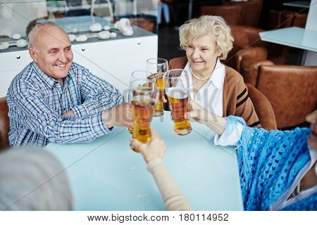 Four cheerful elderly people sitting in cozy pub and clanging beer glasses together with joy