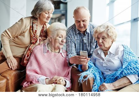 Tech-savvy senior man teaching his female friends how to write SMS message while they gathered together in cafe