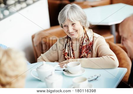 Waist-up portrait of pretty senior woman with wide smile having good time with her best friends while sitting in cozy small coffeehouse