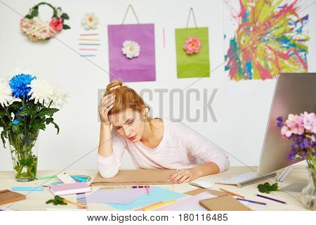Exhausted fashion designer leaning head on hand and feeling lack of creative ideas, messy office table with sketchbook, pencils and color swatches on foreground