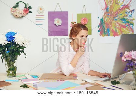 Concentrated young illustrator writing email to her client while holding pencil in hand, sketchbook, color swatch books and other stationery lying on office desk