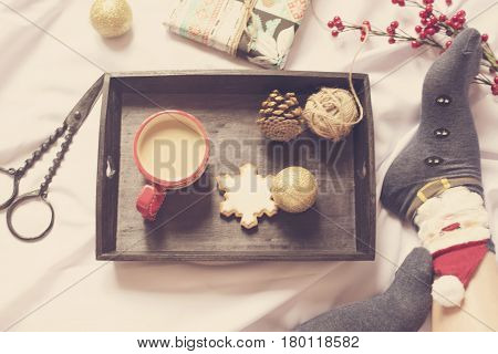 Cute photo of woman's feet with Christmas socks. Girl with presents sitting on a bed. Holiday morning with gifts. A tray with cocoa ginger snowflake biscuit Christmas balls in the bed. Vintage tinting.