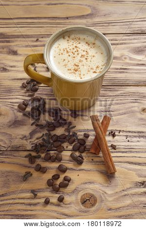 coffee in a yellow mug and coffee beans and cinnamon sticks