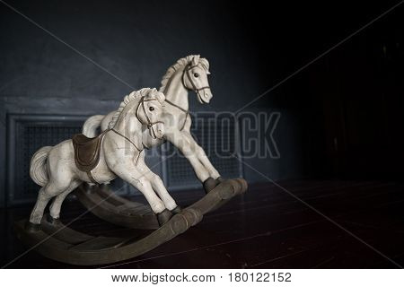 old vintage rocking horse on the background of a chalky wall in the dark interior of the children's room.