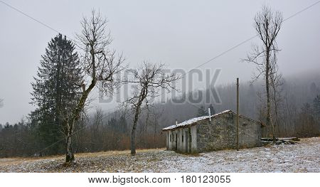 A dusting of snow on an old abandoned stone shack near Canebola in Friuli Venezia Giulia north east Italy