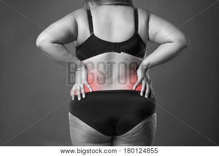 Back pain fat woman with backache overweight female body on gray background black and white photo with red spots