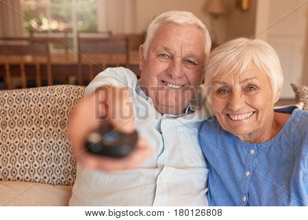 Smiling senior man pointing a remote while sitting with his wife on a couch in their living room watching television together