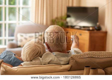 Rearview of an affectionate senior couple relaxing in each other's arms and watching television on a sofa in their living room at home