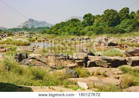Tungabhadra River in Hampi area with Anjaneya hill in the background which is believed to be the birthplace of Hindu God Hanuman.