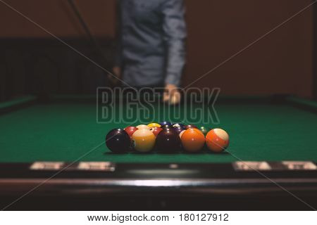 American billiard poule. Shot of a man playing billiard. Triangle of billiard balls.