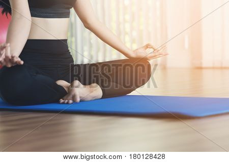 Young Asian woman practicing yoga. Girl is meditating. Copy space.