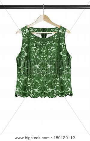 Green lacy sleeveless top on wooden clothes rack isolated over white