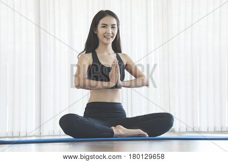 Young Asian woman in prayer position of yoga. Copy space. Happiness smiling.