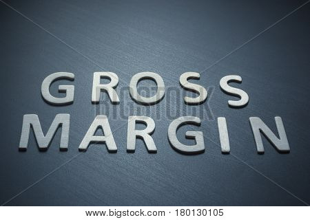 Margin Gross written with wooden letters on a blue background to understand a concept of economics and finance