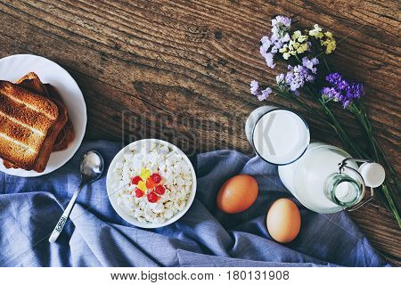 Dairy products on dark wooden table. Sour cream, milk, cheese, egg and Toasts. Top view with copy space.