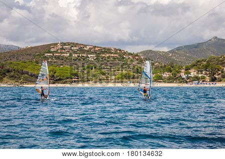 ITALY two man Windsurfing in Sardinia on blue water in front of rocky coast