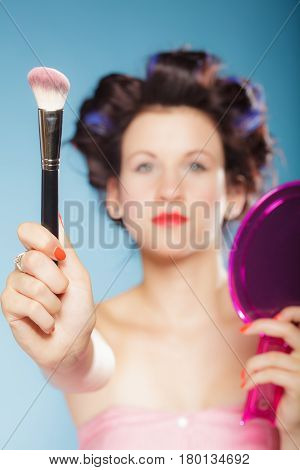Cosmetic beauty procedures and makeover concept. Woman in hair curlers holding makeup brush on blue