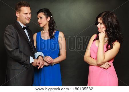 Love triangle concept. Man cheating on his wife looking at other woman choosing between two ladies.