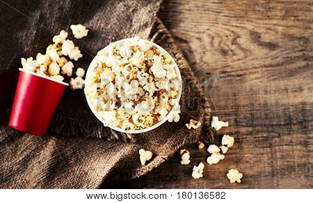 Homemade Popcorn on wooden background - cinema movies and entertainment concept