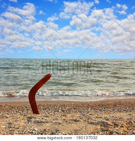 Australian Boomerang on tropical beach against of sea wave and blue sky.