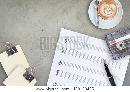 Sheet note fountain pen tape cassette and coffee latte on wooden table top view picture