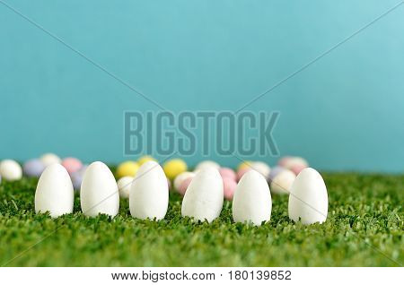 A row of white easter eggs displayed on artificial grass with speckled easter eggs that is out of focus