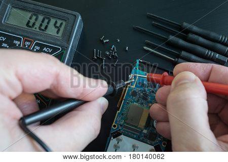 pov shot of technician hands measure voltage, amperage on broken smartphone by multimeter with probes. on black desk
