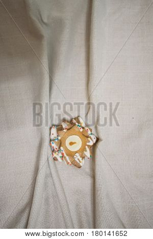 Close up of home made Christmas cookie in shape of star lying on white cloth background