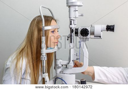 Attentive optometrist examining female patient on slit lamp in ophthalmology clinic