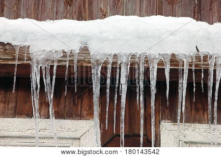 lots of white long icicles on visor of roof of wooden house in spring