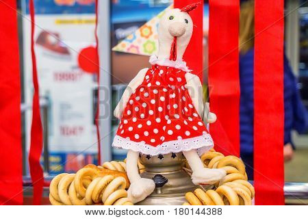 Close up colorful textile hen sitting on samovar with bagels traditional Russian background