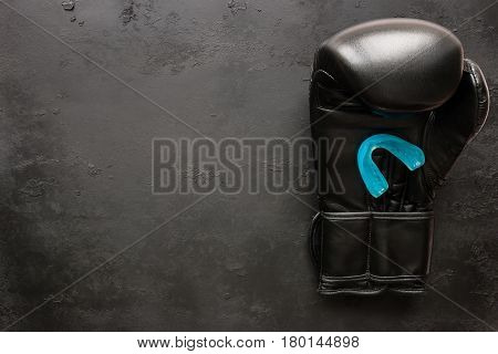 One Boxing Glove And A Mouth Guard On A Black Background With Space For Text