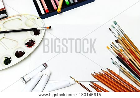 Paints and brushes on white canvas background. art paint brushes and white canvas mock up.